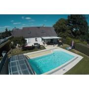 Pergola bioclimatique adossée à côté d'une piscine